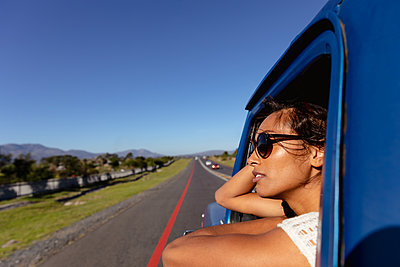 Young woman leaning out of the passenger window of a pick-up truck on the highway - p1315m2130581 by Wavebreak