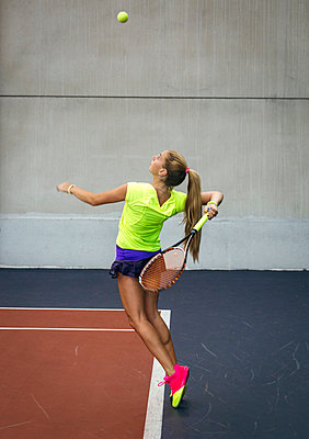 Young woman playing tennis in an indoor tennis center - p300m1058992f by Marco Govel