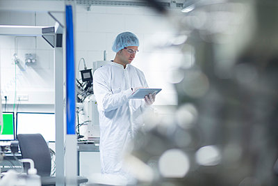 Technician in cleanroom holding digital tablet - p300m998515f by Sigrid Gombert
