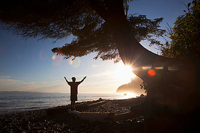 a man raises his arms at sunset; mystic beach, vancouver island, british columbia, canada - p44213176f by Deddeda