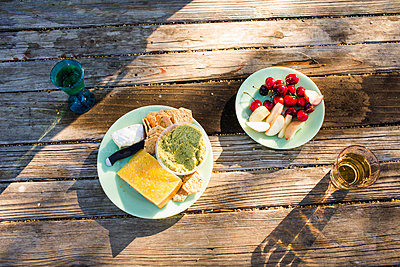 Plates of cheese and fruit on wooden table - p555m1411631 by Adam Hester
