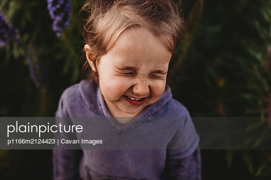 Close up portrait of little toddler girl scrunching nose and laughing - p1166m2124423 by Cavan Images