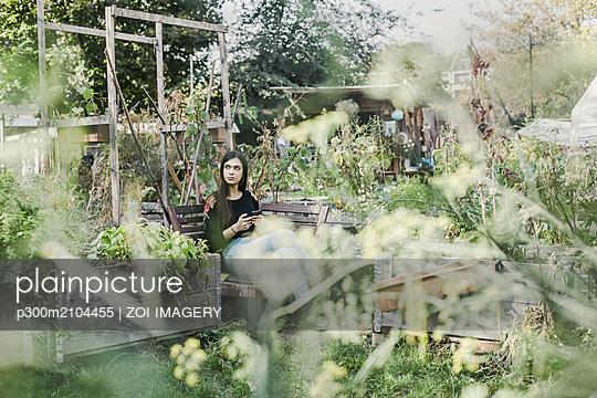 plainpicture - plainpicture p300m2104455 - Woman with smartphone relax... - DEEPOL by plainpicture/ZOI IMAGERY