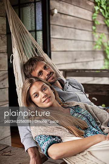 Portrait of couple relaxing in hammock - p623m2258088 by Dinoco Greco