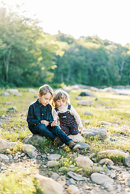 Two siblings talking to each other by the lake - p1166m2208557 by Cavan Images