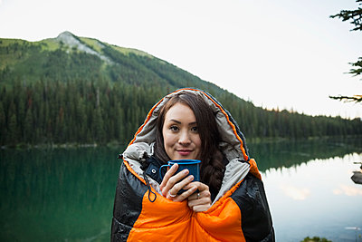Portrait smiling woman drinking coffee standing in sleeping bag at remote lakeside - p1192m1184082 by Hero Images