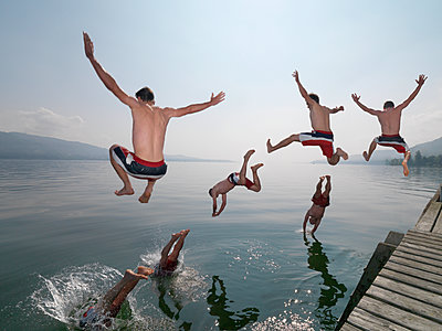 Men Jumping Off Wooden Pier Into Lake - p1531m2264186 by Jens Lucking
