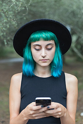 Portrait of young woman with dyed blue and green hair and nose piercing using smartphone - p300m2120811 von Sus Pons