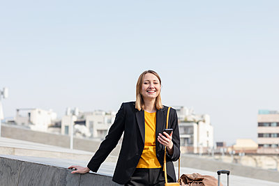 Smiling female entrepreneur standing with mobile phone - p300m2274329 by Emma Innocenti