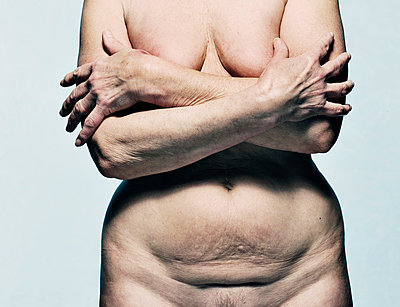Nude older woman covering her breasts - p429m713091 by Colin Hawkins