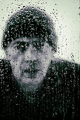 Man looking through rain splattered window - p597m2063523 by Tim Robinson