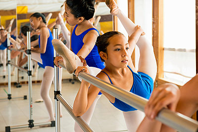 Ballerinas warming up at the barre in ballet school - p924m825939f by Florin Prunoiu