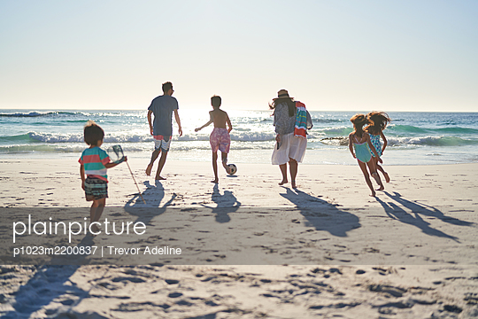 Family running and playing soccer on sunny ocean beach - p1023m2200837 by Trevor Adeline