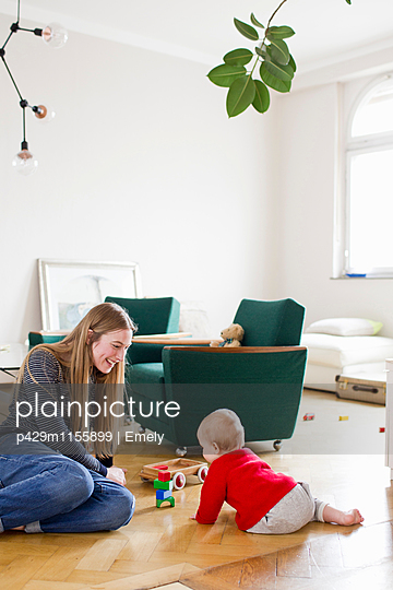 Mid adult woman and baby daughter play with building blocks on living room floor - p429m1155899 by Emely