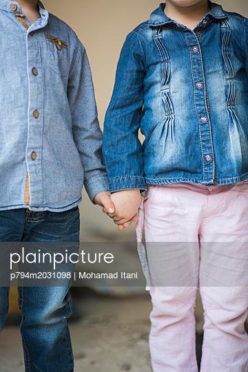 Junge und Mädchen halten sich an den Händen - p794m2031098 von Mohamad Itani
