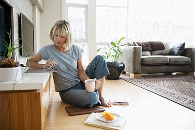 Woman working from home, using digital tablet on living room floor - p1192m2088356 by Hero Images