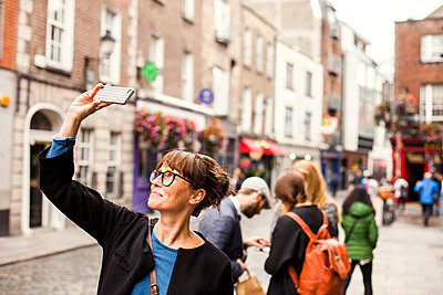 Smiling woman taking selfie with friends standing in background on city street - p1264m1122068f by Astrakan