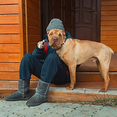 Man with dog sitting in the doorway - p1476m2026985 by Yulia Artemyeva