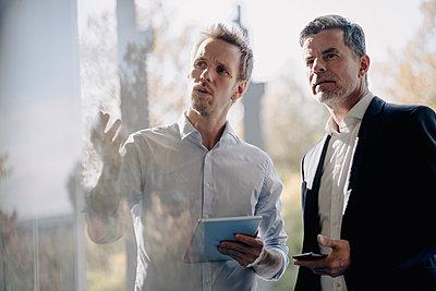 Two businessmen talking at the window - p300m2170402 by Kniel Synnatzschke