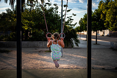 Girl hanging on gymnastic rings on playground at park - p300m2250753 by Albert Martínez