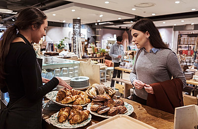 Saleswoman showing baked food to female customer at cafe - p426m2035341 by Kentaroo Tryman