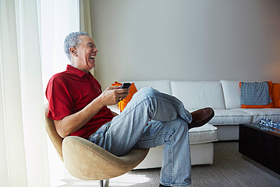Older Black man using cell phone in living room - p555m1411581 by Jasper Cole