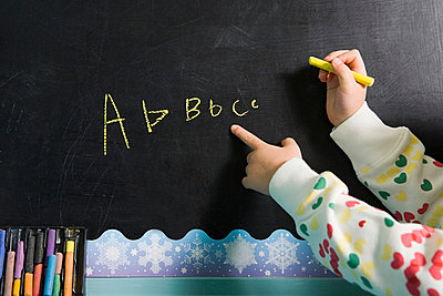 Girl writing on a blackboard - p9248481f by Image Source