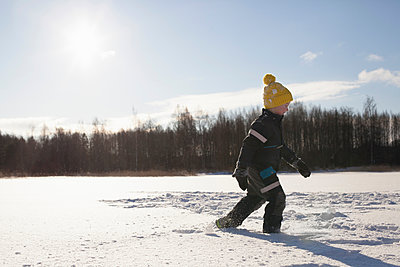 Young boy walking in snow covered landscape - p924m1422672 by Tiina & Geir