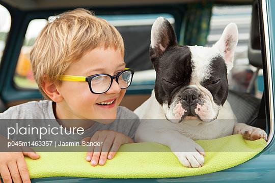 Junge und Hund schauen aus dem Autofenster - p045m1463357 von Jasmin Sander
