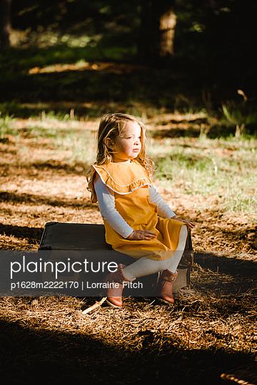 Kleines Mädchen im gelben Kleid sitzt auf einem Koffer - p1628m2222170 von Lorraine Fitch