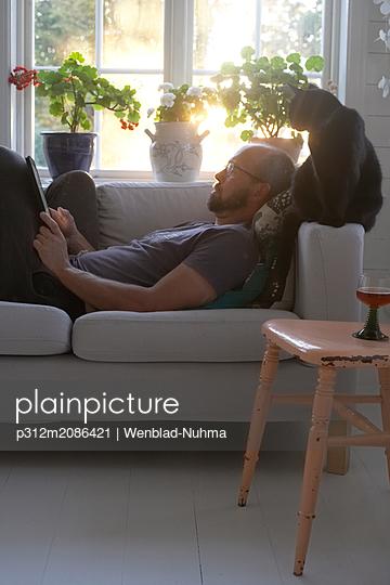 Man using tablet on sofa - p312m2086421 by Wenblad-Nuhma