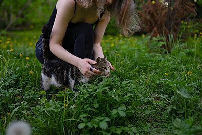 Young woman playing with cat - p1646m2264261 by Slava Chistyakov