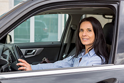 Portrait of smiling woman driving car - p300m2012679 by JLPfeifer