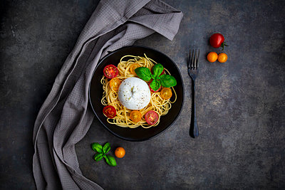 Spaghetti with tomatoes, burrata and basil leaves, from above - p300m2083731 by Larissa Veronesi
