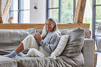 Smiling mature woman holding coffee cup while sitting on sofa at home - p300m2241253 by Maya Claussen