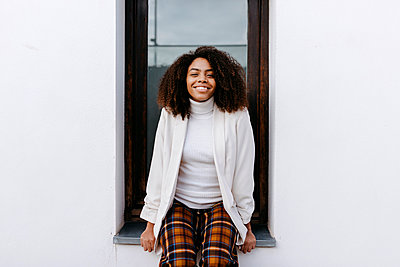 Smiling young woman with afro hair sitting on window sill - p300m2257302 by Tania Cervián