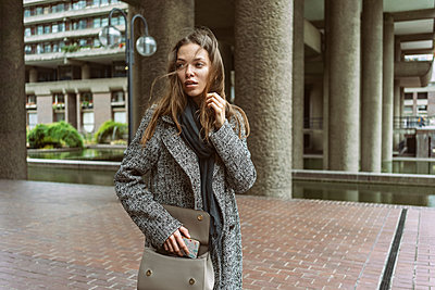 Young woman on walkway of office building, London, UK - p429m2075422 by Tamboly
