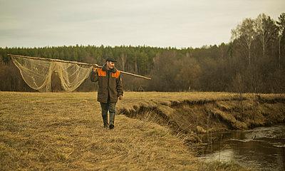 Mature man walking along riverbank carrying traditional fishing net - p429m859934 by Aleksander Rubtsov