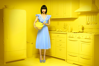 Caucasian woman in yellow old-fashioned kitchen holding mixing bowl - p555m1304585 by Chris Clor