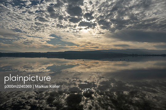 Gray clouds reflecting in Lake Constance at dusk - p300m2240369 by Markus Keller