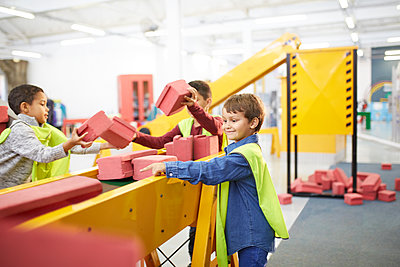 Kids playing with toy bricks at interactive construction exhibit in science center - p1023m2016877 by Trevor Adeline