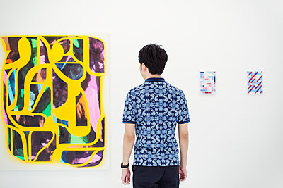 Rear view of man with short black hair wearing blue shirt standing in art gallery, looking at abstract modern painting. - p1100m1531064 by Mint Images