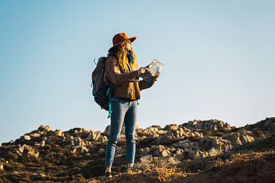 Italy, Sardinia, woman holding map on a hiking trip - p300m1580825 von Kike Arnaiz