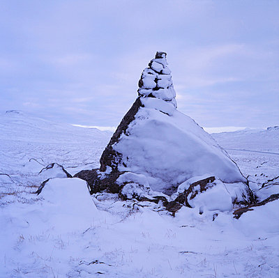 A stone cairn covered in snow in wintertime - p3487922 by Bjarki Reyr Asmundsson