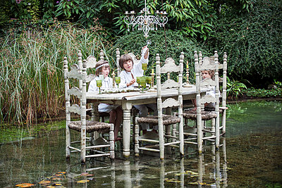 Children seated at ornate dining table floating on lake - p675m922838 by Odilon Dimier