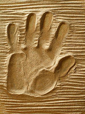 Hand in sand - p676m2263904 by Rupert Warren