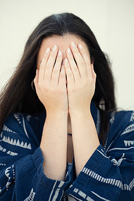 Sad young woman hiding face with hands  - p794m2260355 by Mohamad Itani