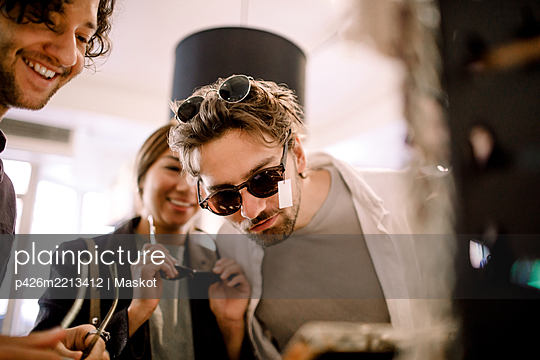 Smiling man trying fashionable eyeglasses with friends at store - p426m2213412 by Maskot