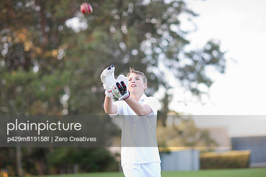 Boy catching cricket ball