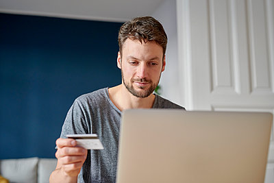 Young man at laptop holding credit card - p1124m1589421 by Willing-Holtz